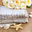 Stack of old letters and bouquet of pastel yellow roses on wood — Stock Photo #29080911