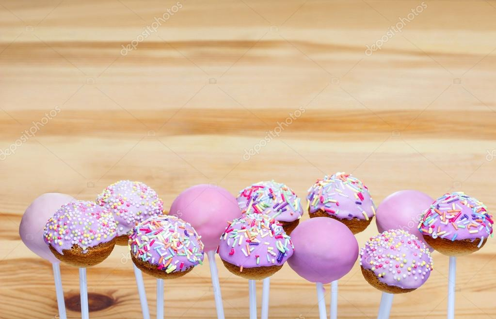 Download - Pink cake pops on wooden background. Copy space — Stock ...