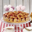 Stock Photo: Strawberry pie on cake stand, checkered red table cloth