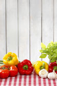 Fresh vegetables on red checkered table cloth. Wooden background — Stock Photo