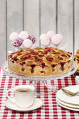 Strawberry pie on cake stand, checkered red table cloth — Stock Photo