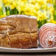 Smoked ham on wooden table. Yellow daffodils in the background. — Stock Photo