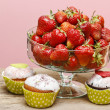 Glass bowl of strawberries and colorful muffins on wooden table. — Stock Photo