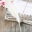 Stack of old letters, feather pen and bouquet of pink carnations — 图库照片