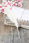 Stack of old letters, feather pen and bouquet of pink carnations — Stock Photo