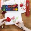 Professional artist painting a rose on white sheet of paper — Stock Photo