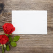 Red roses on wooden background. Blank sheet of paper. Copy space — Stock Photo