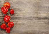červené papriky na starý dřevěný stůl. prázdná deska, kopie prostor. — Stock fotografie