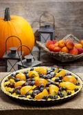 Koláč s broskví, dýně, švestek a borůvek v podzimní prostředí — Stock fotografie
