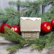 Stock Photo: Gingerbread house on fir branch among red apples.