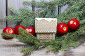 Gingerbread house on fir branch among red apples. — Stock Photo