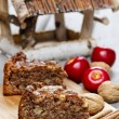 Cinnamon cake on wooden tray. Red apples and nuts in the back — Stock Photo #30010157