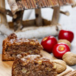 Cinnamon cake on wooden tray. Red apples and nuts in the back — Stock Photo