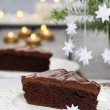 Piece of chocolate cake in white christmas table setting — Stock Photo