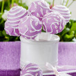 Lilac cake pops in white ceramic jar. White and pink daisies — Stock Photo #30013143