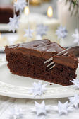 Piece of chocolate cake in white christmas table setting — Stock fotografie