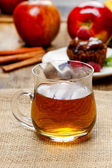 Glass of hot steaming tea on hessian napkin. Red apples — Stock Photo