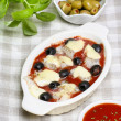 Cheese, tomato sauce and black olives gratin on checkered table — Stock Photo