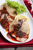 Plaice with red sauce on white plate — Stock Photo