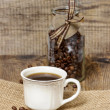 Cup of coffee on hessian napkin. Coffee beans around. Selective — Stock Photo