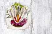 Top view of pickled herring with fresh vegetables on white woode — Stock Photo