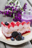 Pink layer cake decorated with fresh fruits on wooden table — Stock Photo