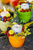 Candle holder decorated with autumn flowers and other plants — Stock Photo