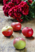 Red apples on wooden table. Aster flowers in the background — Stock Photo