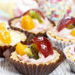 Cupcake with fresh fruits. Diversity of sweets in the background — Stock Photo