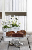 Chocolate cake on glass stand, on grey wooden table — Stock Photo