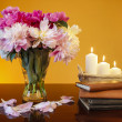 Bouquet of peonies in glass vase and basket of candles on wooden — Stock Photo