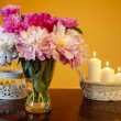 Stock Photo: Bouquet of peonies in glass vase and basket of candles on wooden