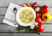 Top view of broth in white bowl on grey rustic wooden table. Col — Stock Photo