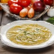 Broth in white bowl on brown rustic wooden table. Colorful veget — Stock Photo