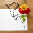 Colorful roses and black rosary on wooden background. Blank shee — Stock Photo