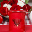 Red iron lantern with heart shape. Basket of roses in the backgr — Stock Photo