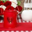 Stock Photo: Red iron lantern with heart shape. Basket of roses in the backgr