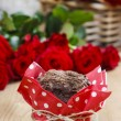 Stock Photo: Chocolate muffins on party table. Basket of red roses in the bac