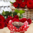 Chocolate muffins on party table. Basket of red roses in the bac — Stock Photo
