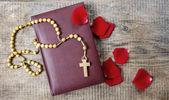 Holy Bible, rosary and red rose petals on wooden table. Copy spa — Stock Photo