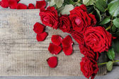 Stunning red roses on wooden table — Stockfoto