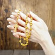 Stock Photo: Hands holding wooden rosary