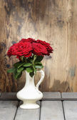 Stunning roses in ceramic vase. Beautiful bouquet on rustic wood — Stock Photo