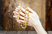 Hands holding wooden rosary — Stock Photo
