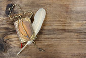 Book, rosary and feather on wooden rough background. Copy space. — Stockfoto