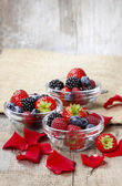 Fruit salad in small transparent bowls on wooden table — Stock Photo