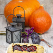 Plum galette on wooden table. Raw plums and pumpkins in the back — Stock Photo #38635867