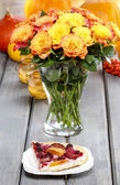 Piece of cake and huge bouquet of orange roses on wooden table. — Stock Photo