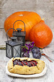 Plum galette on wooden table. Raw plums and pumpkins in the back — Stock Photo