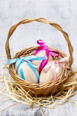 Easter wicker basket of eggs on grey background. Copy space — Stockfoto